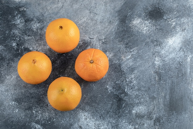 Vier leckere orangen auf marmortisch.
