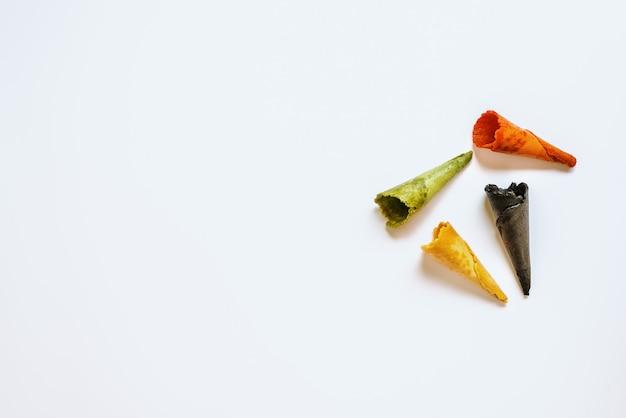 Vier leere eiscremewaffeln der verschiedenen farben und der aromen getrennt