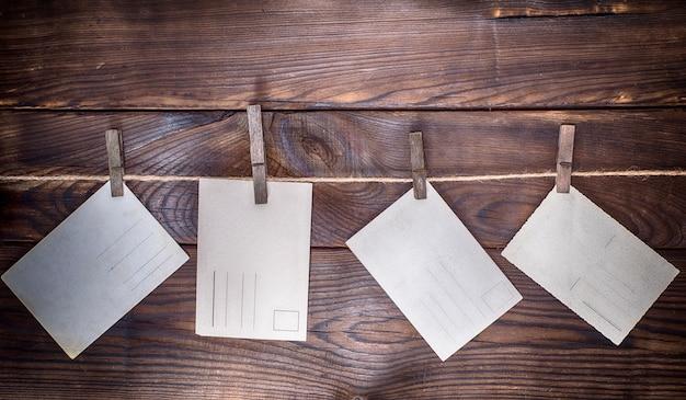 Vier leere papierpostkarten hängen an einem seil