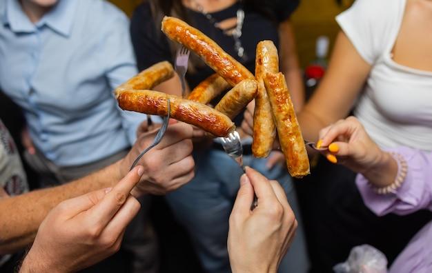 Vier leute halten zusammen einen hot dog.