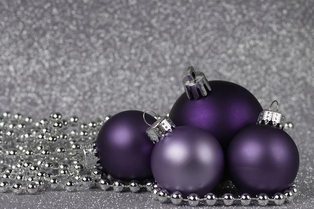 Vier lila weihnachtskugeln auf einem glänzenden silbernen hintergrund mit silberner perlenweihnachtszusammensetzung
