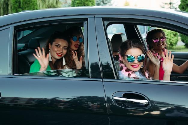 Vier mädchen mit sonnenbrille auf modischem schwarzen auto, verabschieden sich und verlassen das haus nach dem einkaufen und ausruhen. das konzept, mit freunden zu entspannen, mit freunden einzukaufen