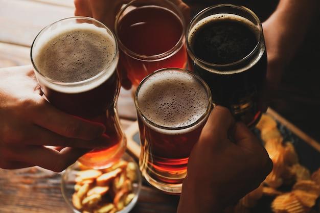 Vier männer jubeln mit bier auf holz mit snacks