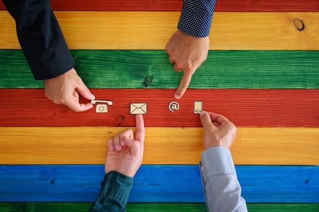 Vier männliche hände, die kontakt- und kommunikationssymbole des papierschnittes in einer reihe auf ein buntes holzbrett setzen. draufsicht.