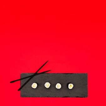 Vier maki rollen in einer reihe mit gurke auf schwarzem schieferstein über roter oberfläche