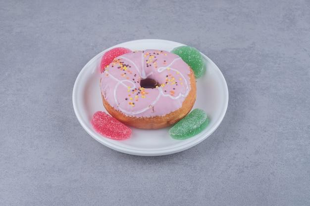 Vier marmeladen und ein donut auf einer platte auf marmoroberfläche