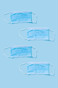Vier medizinische masken auf blauem hintergrund zum schutz von mund und nase zum schutz vor viren und bakterien. epidemie-konzept. einfaches muster, flache lage.