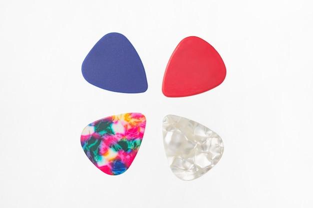 Vier mehrfarbige plektren zum gitarrespielen. auf weißem hintergrund