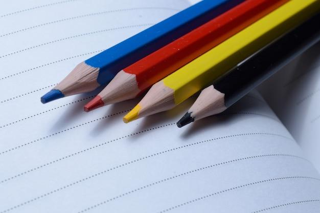 Vier mehrfarbige stifte - blau, rot, gelb, schwarz. auf einem offenen notizbuch liegen.