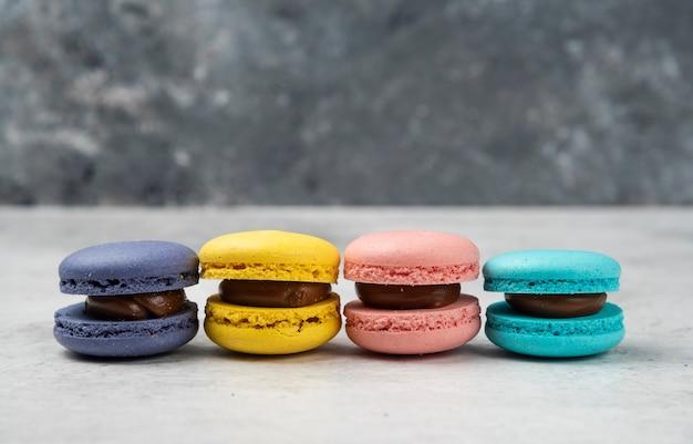 Vier mehrfarbiges macarons-dessert auf weißem tisch.