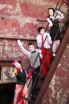 Vier mimen stehen auf der treppe an einer roten wand.