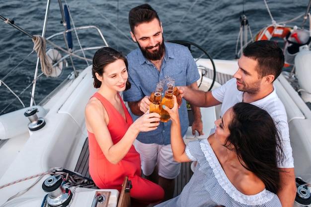 Vier nette leute stehen und halten flaschen mit alkohol ganz nah. sie schauen es sich an und lächeln. paare verbringen zeit miteinander.