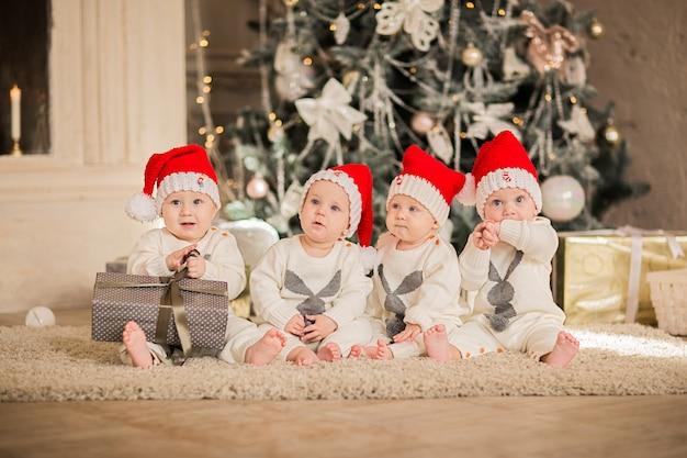 Vier neugeborene kinder in santas mützen sitzen auf dem boden