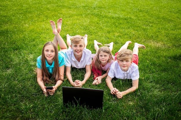 Vier niedliche kinder, die auf grünem gras mit laptop liegen