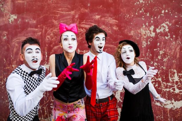 Vier pantomimen, die beiseite auf dem hintergrund einer roten wand schauen