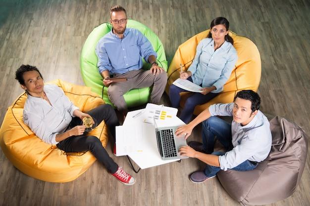 Vier personen arbeiten und sitzen auf sitzsäcken