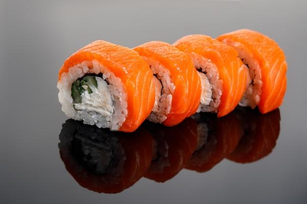 Vier philadelphia sushi rolle auf einem glastisch.