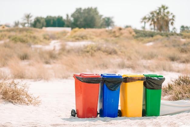 Vier plastikbehälter zum müllsortieren am strand.