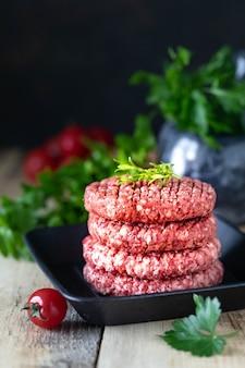 Vier rohe burgerschnitzel mit gehacktem fleisch mit salz, kräutern und gewürzen in einer grillpfanne
