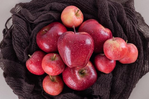 Vier rote äpfel auf braunem stoff.