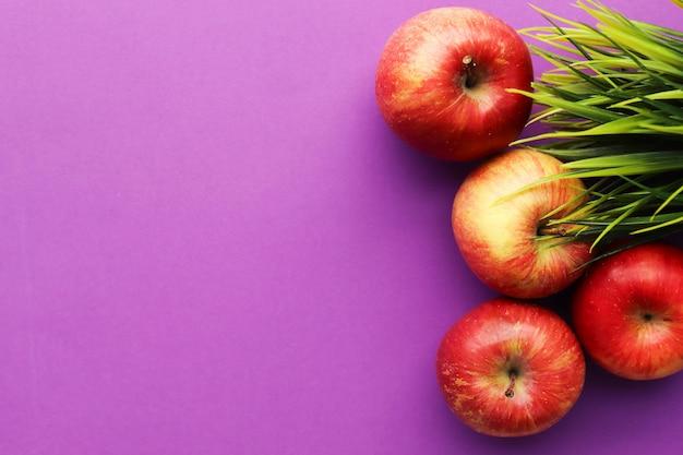Vier rote äpfel auf lila oberfläche