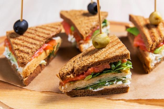 Vier sandwiches auf holztisch in einem restaurant. fast food