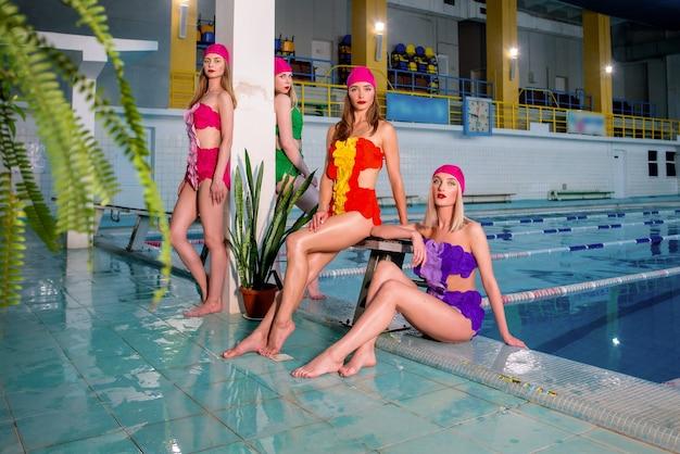 Vier schlanke junge stylische frauen in bunten badeanzügen und rosa bademützen im schwimmbad