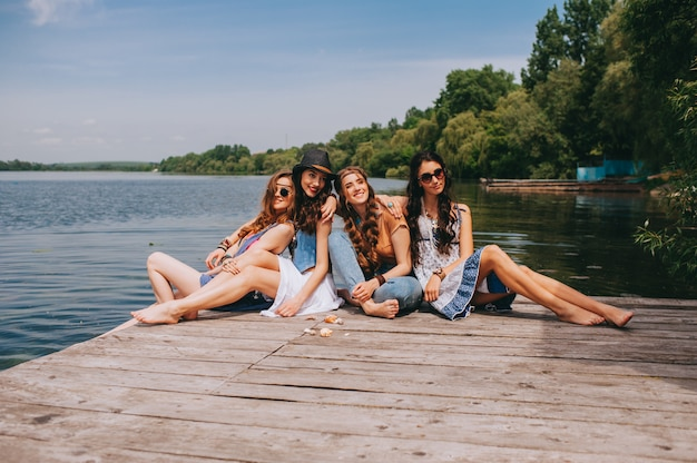 Vier schöne freundinnen auf dem dock