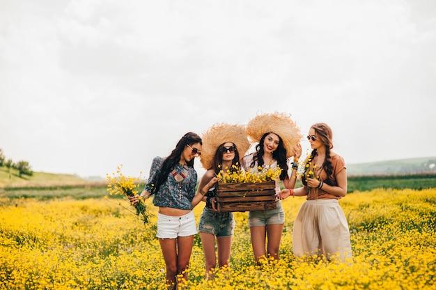 Vier schöne hippie-mädchen in einem feld von gelben blumen