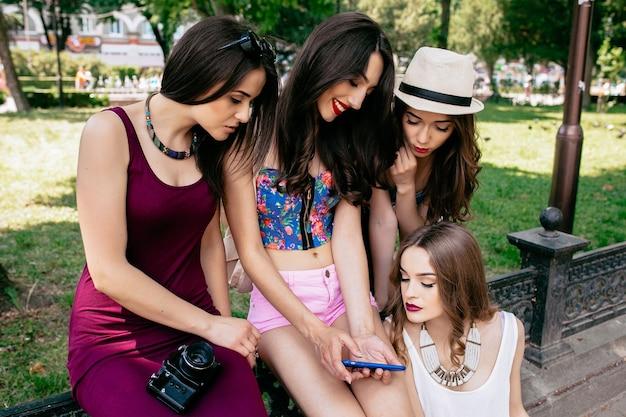 Vier schöne junge frauen, die die fotos auf einem smartphone im park betrachten
