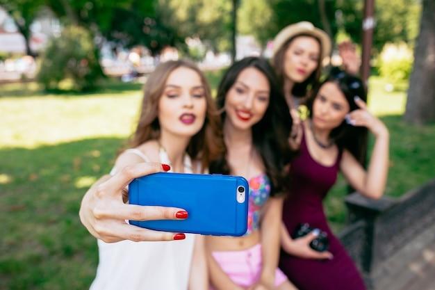 Vier schöne junge frauen machen selfie im park