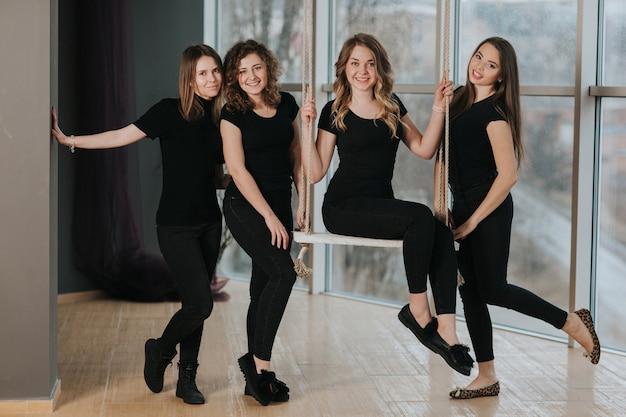 Vier schöne mädchen in schwarzer aufstellung