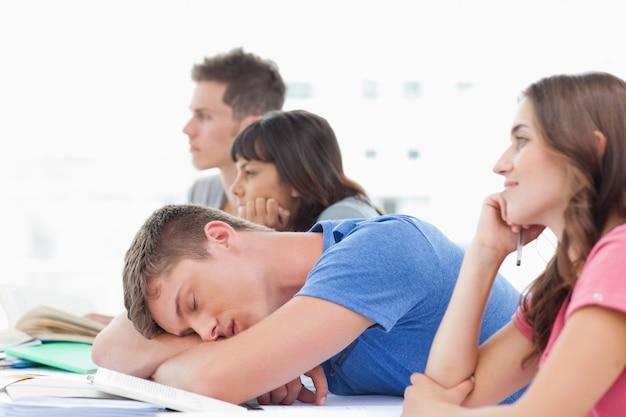 Vier schüler in der klasse als drei achten darauf, dass ein männlicher student schläft
