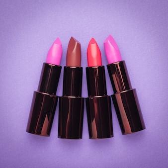 Vier stilvolle lippenstifte auf einem lila tisch. lippendekoration. flach liegen.