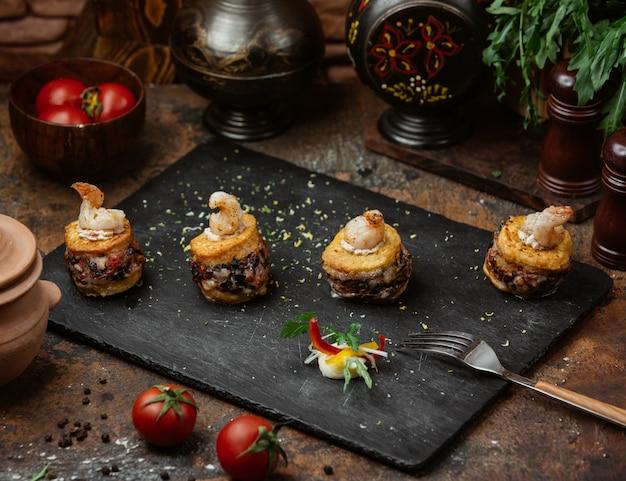 Vier stücke mini-beilagen in sadwich-form auf steinbrett