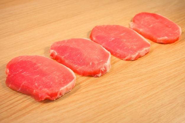 Vier stücke schweinefleisch auf einem holzbrett mit einem brett geschnitten.