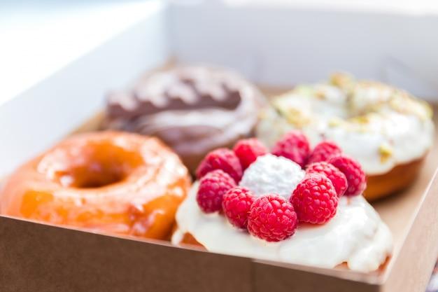 Vier stücke völlig unterschiedlicher bunter und köstlich aussehender donuts im ökologischen karton. appetitliches fast-food-dessert