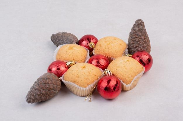 Vier süße cupcakes mit tannenzapfen und weihnachtskugeln