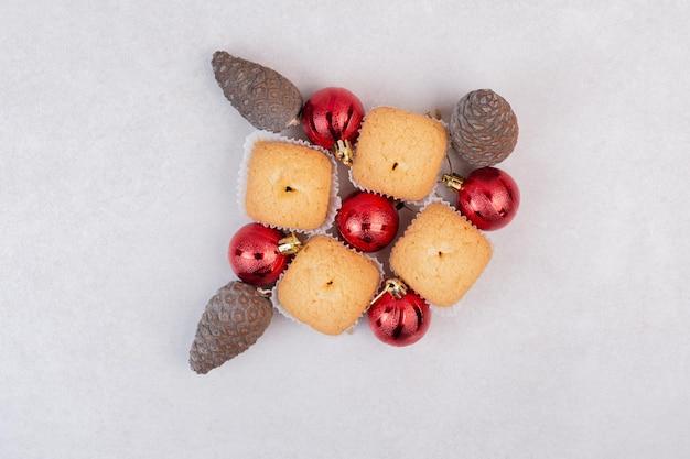Vier süße cupcakes mit tannenzapfen und weihnachtskugeln.