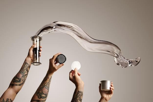 Vier tätowierte hände halten aeropresse und ersatzteile mit wasser, das aus aeropresse auf weißem alternativem kaffeebrühwerbespot herausfliegt