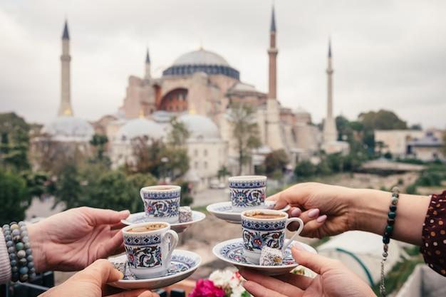 Vier tassen türkischen kaffees in der menschenhand auf hagia sophia hintergrund, istanbul