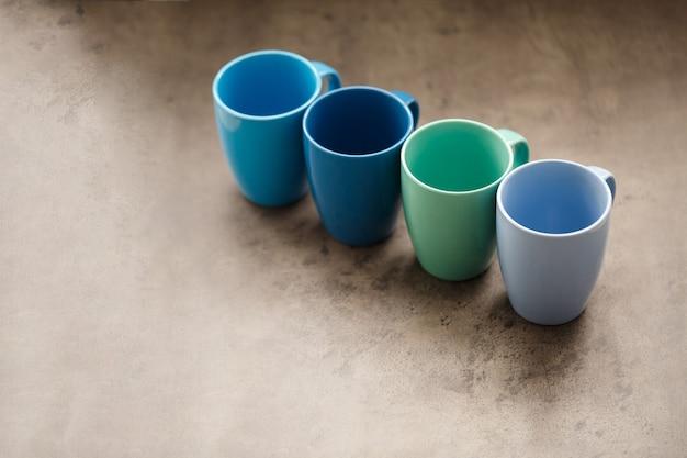 Vier teebecher in verschiedenen farben auf grauem hintergrund
