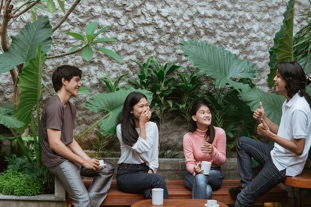 Vier teenager, die beim sitzen auf tisch und holzbank im hausgarten plaudern
