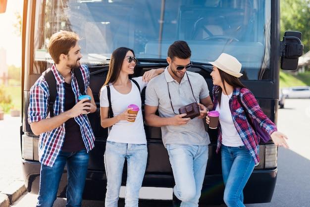 Vier touristen posieren vor einem schwarzen bus