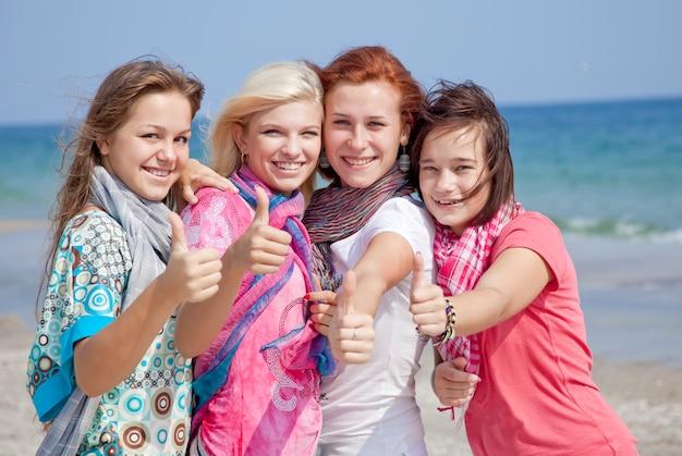 Vier umarmende freundinnen am strand zeigen okaysymbol.
