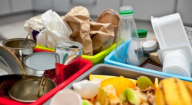 Vier verschiedene behälter zum sortieren von müll. für kunststoff-, papier-, metall- und organische abfälle