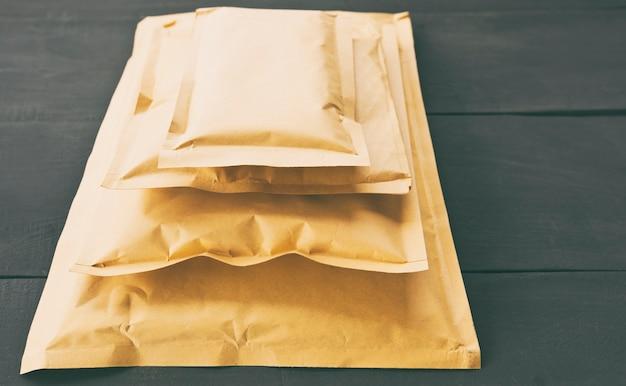 Vier verschiedene papierumschläge auf dem holztisch