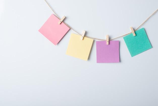 Vier verschiedenfarbige papiere am seil mit kopierraum für die beschriftung auf einer weißen tafel