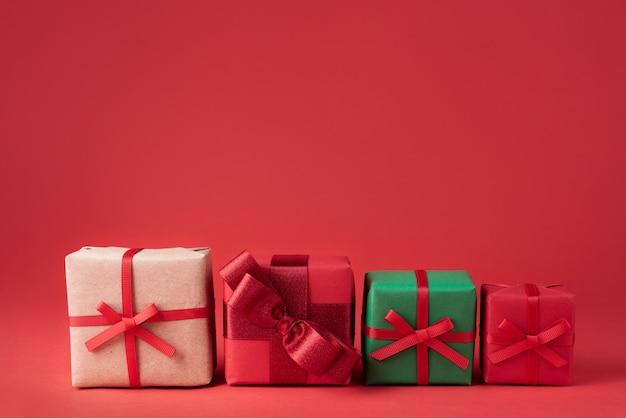 Vier weihnachtsgeschenke in bunten verpackungen auf rotem hintergrund nahaufnahme