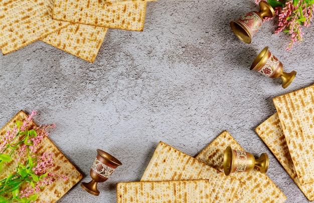 Vier weinbecher mit matze. jüdische feiertage pessach konzept.
